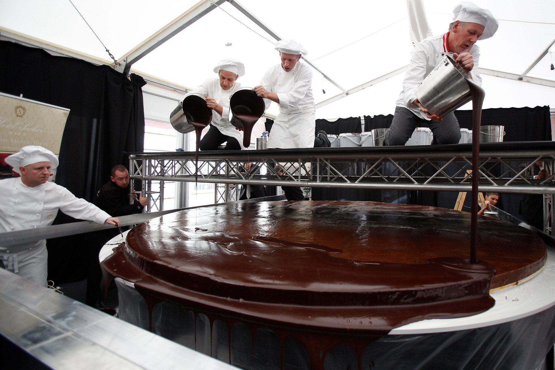 Confectioners glaze the world's largest original Sacher-torte with chocolate in Ljubljana, Slovenia, Sept. 21, 2016. The largest original Sacher-cake was made to mark the ending of the Vienna Days in Ljubljana.
