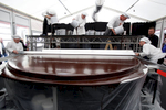 Confectioners glaze the world's largest original Sacher-torte with chocolate using a special platform and spatula in Ljubljana, Slovenia, Sept. 21, 2016. The largest original Sacher-cake was made to mark the ending of the Vienna Days in Ljubljana.