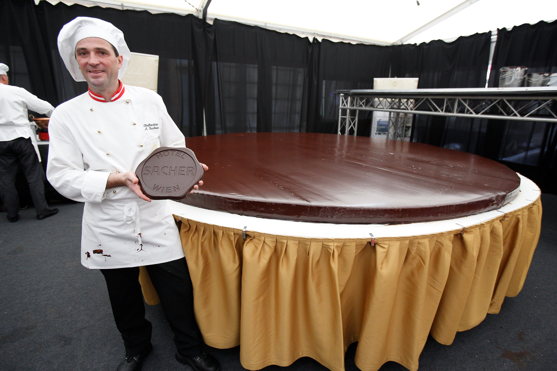 Head confectioner Alfred Buxbaum poses with the chocolate emblem that will be placed on top of the world's largest original Sacher-torte as a final touch in Ljubljana, Slovenia, Sept. 21, 2016. The largest original Sacher-cake was made to mark the ending of the Vienna Days in Ljubljana.