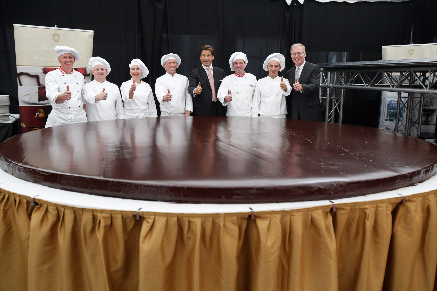 Confectioners, Sacher family member Matthias Winkler and managing director of Sacher Hotel Vienna Reiner Heilmann (far right) pose the world's largest original Sacher-torte in Ljubljana, Slovenia, Sept. 21, 2016. The largest original Sacher-cake was made to mark the ending of the Vienna Days in Ljubljana.