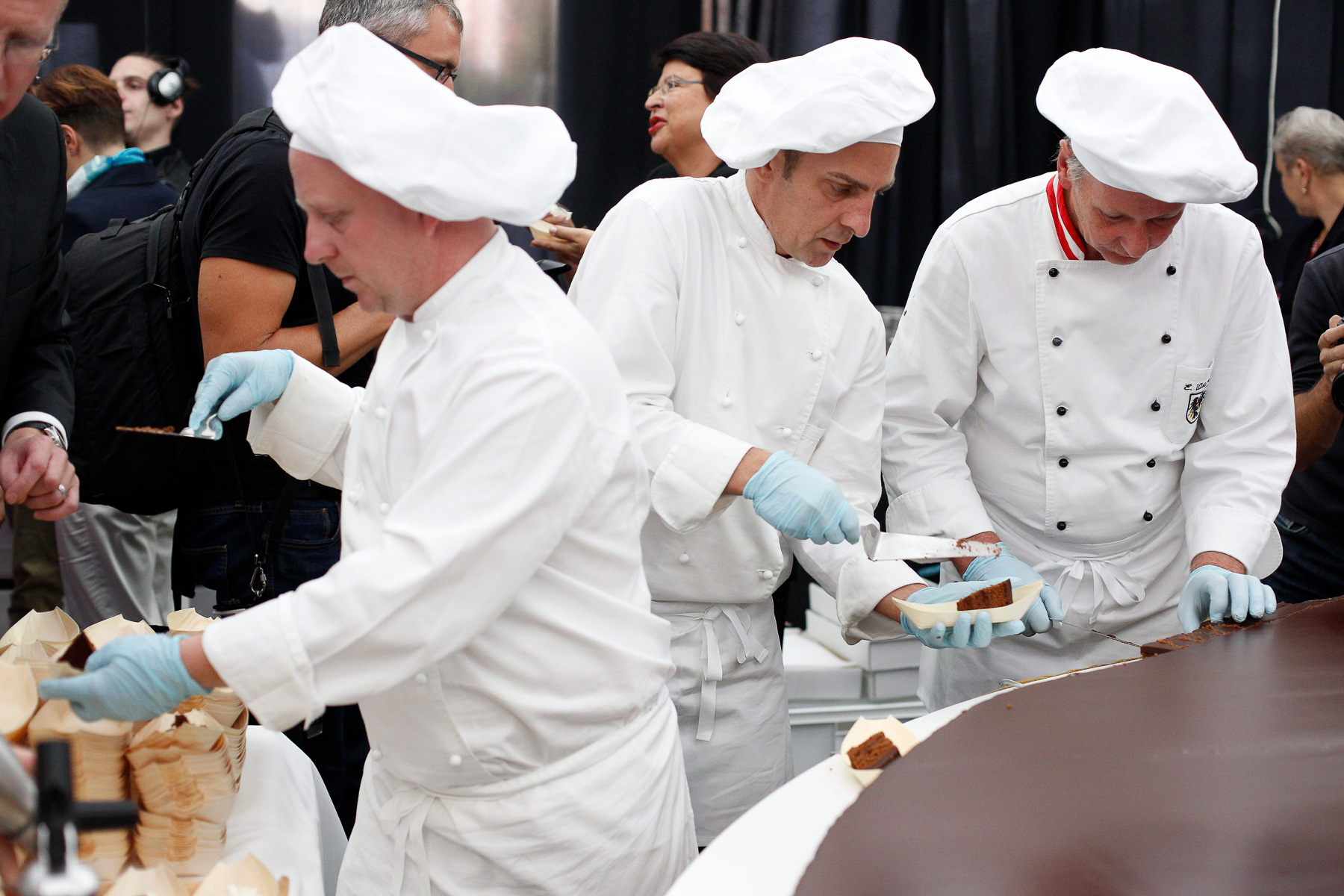 Confectioners cut portions of the world's largest original Sacher-torte to serve to the citizens in Ljubljana, Slovenia, Sept. 21, 2016. The largest original Sacher-cake was made to mark the ending of the Vienna Days in Ljubljana.