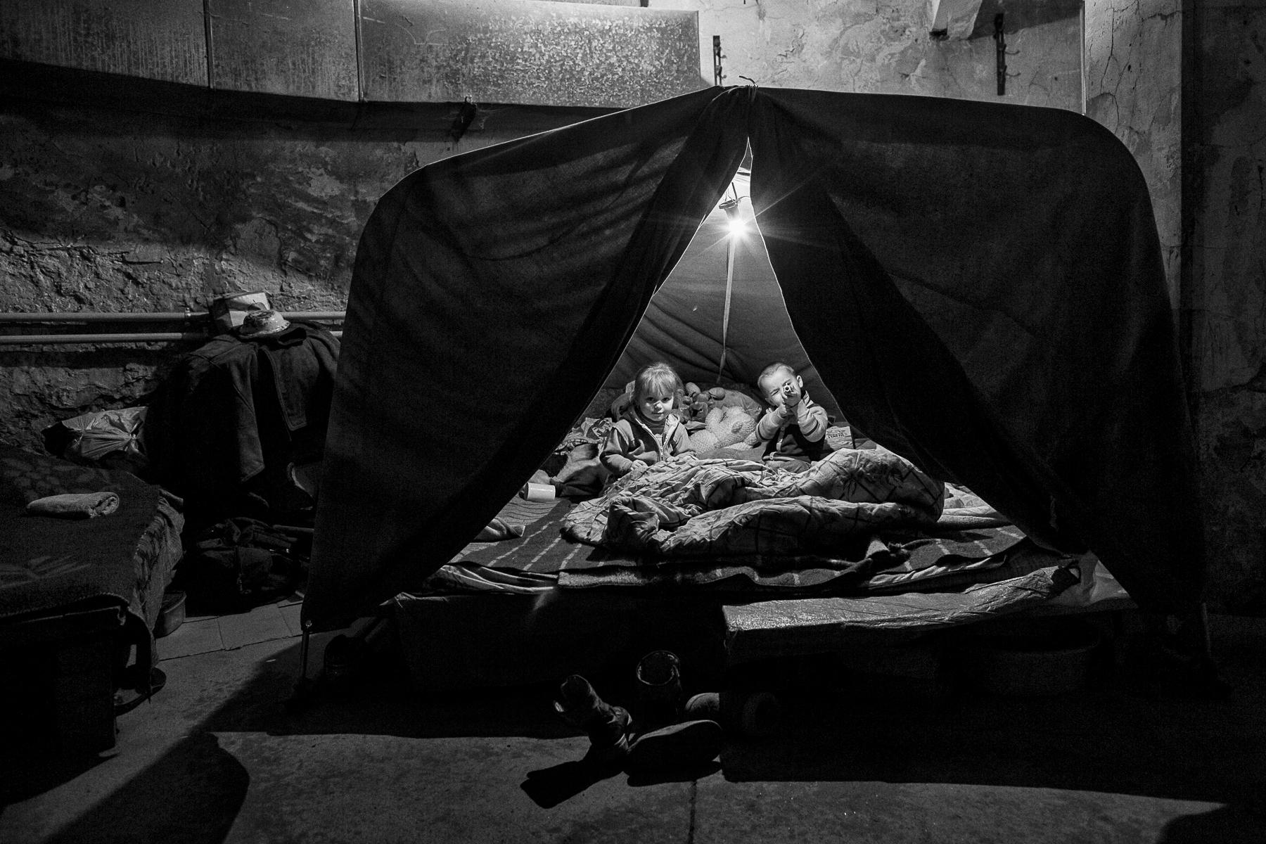 A Petrovski, quartier à l\'ouest de Donetsk,  quotidiennement bombardé par l\'armée ukrainienne, entre 200 et 500 personnes vivent depuis juillet 2014 dans les caves de la maison de la culture.Lila, 3ans et demie à gauche et Nikita, 4 ans, à droite jouent sous leur \{quote}tente\{quote}, un abri sommaire couvert de draps, dans les sous-sols de la maison de la culture.