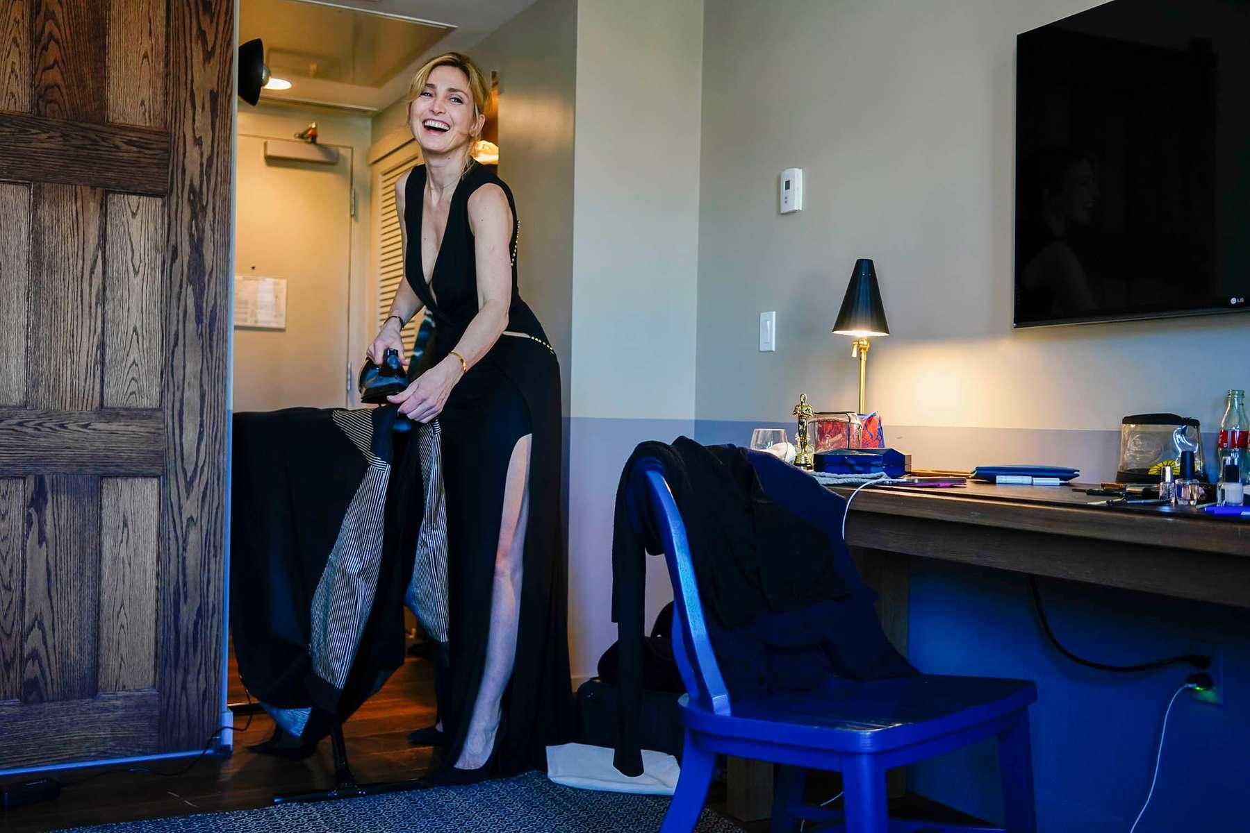 Julie Gayet dans sa chambre de l'hôtel Roosevelt à Hollywood, quelques heures avant la cérémonie des Oscars, repasse la robe de son associée Nadia Turincev. Elle porte une robe Elie Saab.