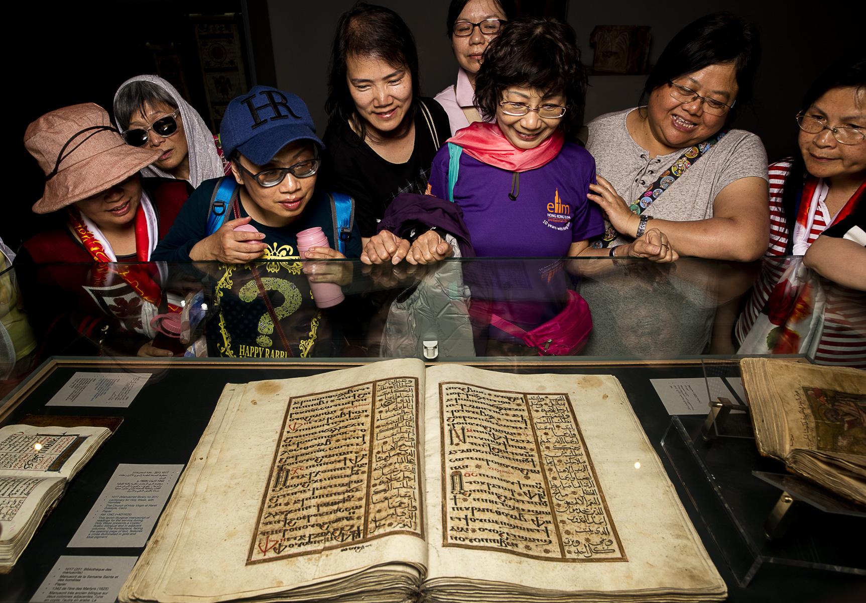 Le Caire, Mars 2016. Un groupe de touristes chinois de Hong Kong, rares touristes à s'aventurer dans le quartier Copte, en admiration devant le manuscrit de la semaine Sainte et des homélies de 1342 .
