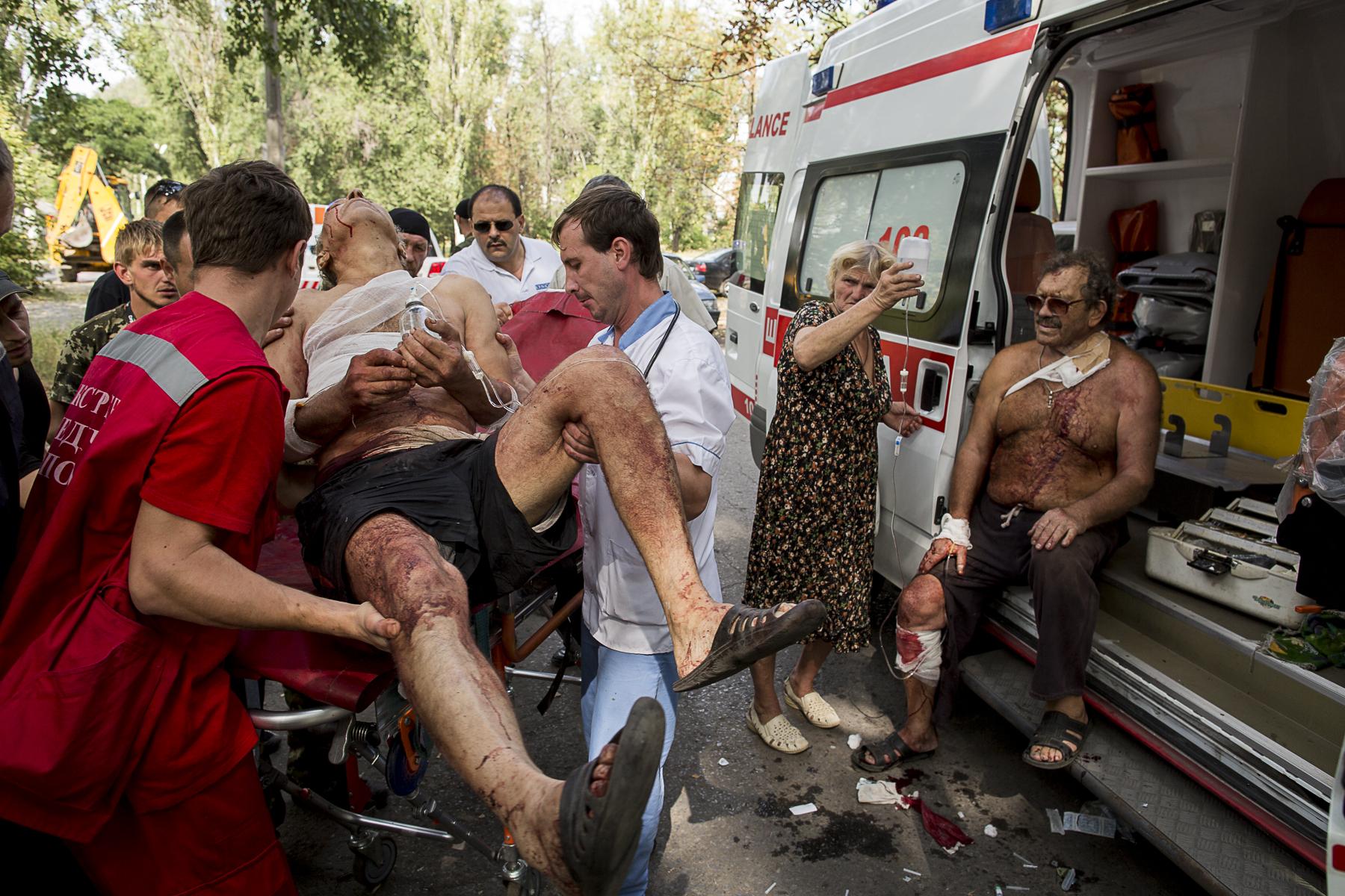 Dans le quartier de Troudovsky le Pope Alexander,ainsi que sa femme et des voisins se cachent dans un abris au cours d\'un bombardement de l\'armée, son église est partie en fumée quelque heures plus tôt./ Enterrement de la famille Kovalenko, tuée trois jours plus tôt (samedi 23) le père Alexandre, 37, la mère Irina 27 Kristina 1à ans et Alexandra presque 6 ans, ils profitaient de la fin d\'après-midi dans le parc devant leur imeuble quand ils furent tués par le bombardement...