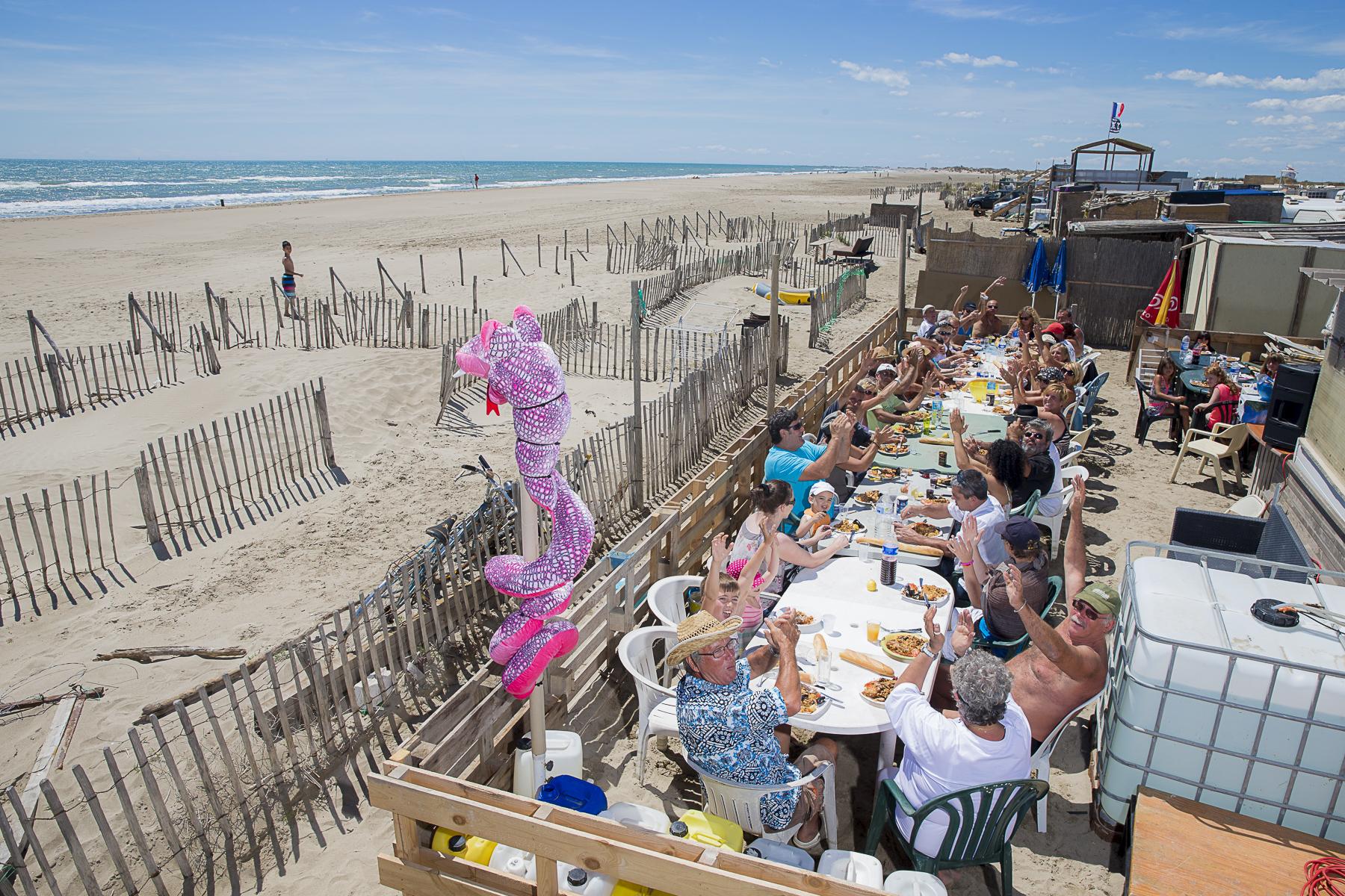 La plage de Piémenson à l\'embouchure du Rhône est la dernière plage en Europe ou le camping sauvage est toléré. Les deux grandes communautées présentent sont les naturistes, très soucieux de l\'environnement et passés maîtres dans l\'art de la construction de cabanons en bois flotés et les \{quote}textils\{quote} vivant plutôt dans des caravannes, ils sont des bons vivants...Paella sur la plage organisée par Marie et son mari Léo