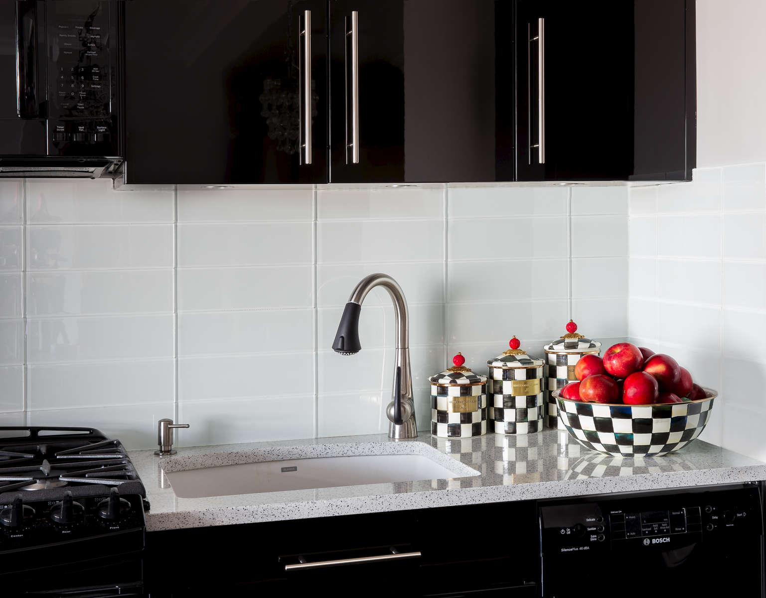 Black lacquered kitchen cabinetry with glass back-splash