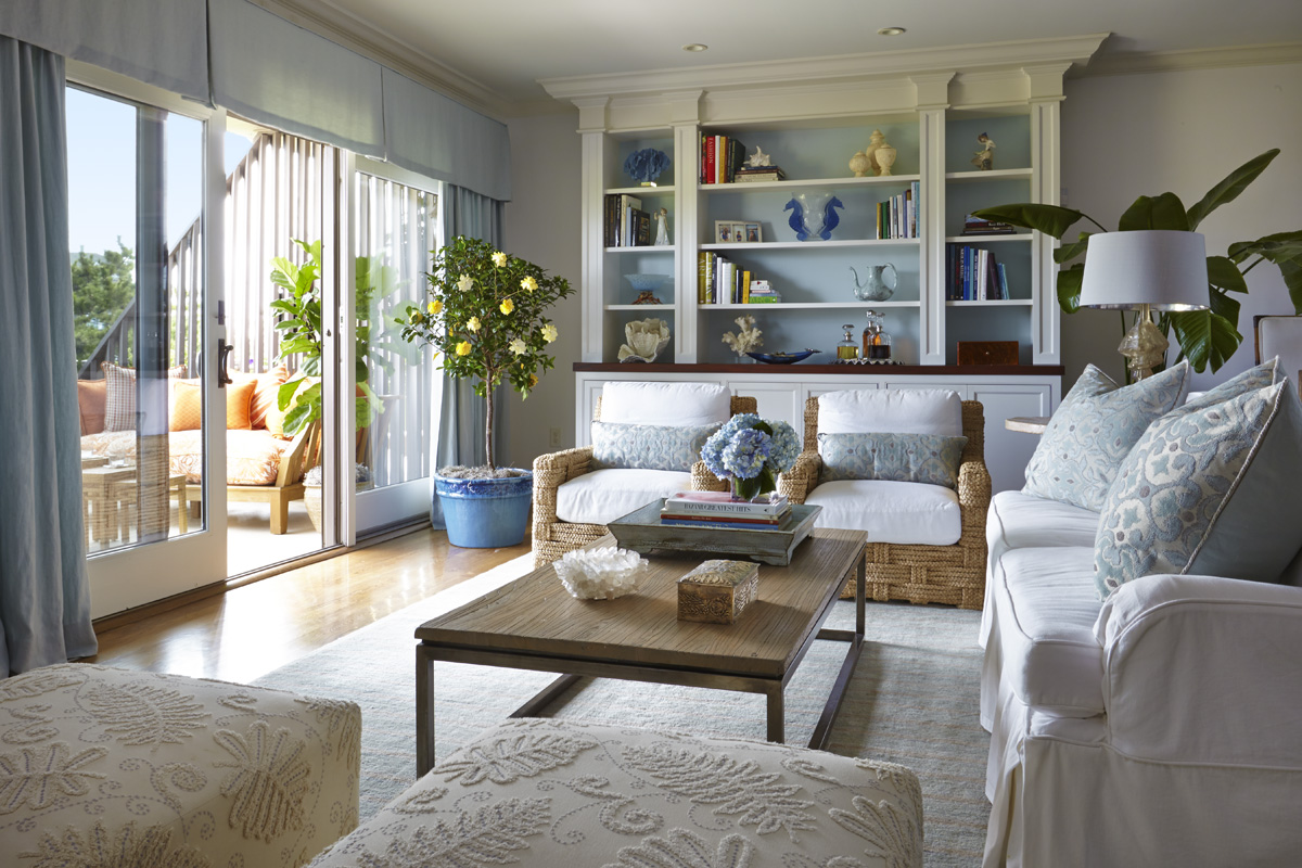 Beach house built-in painted white and blue. A cool palette of blues and whites set the tone for this waterfront home. A U-shape seating arrangement allows for views to the television and the outdoor terrace.