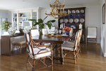 Dining Room Design  with spanish style table juxtaposes the light bamboo chairs and chandelier above.