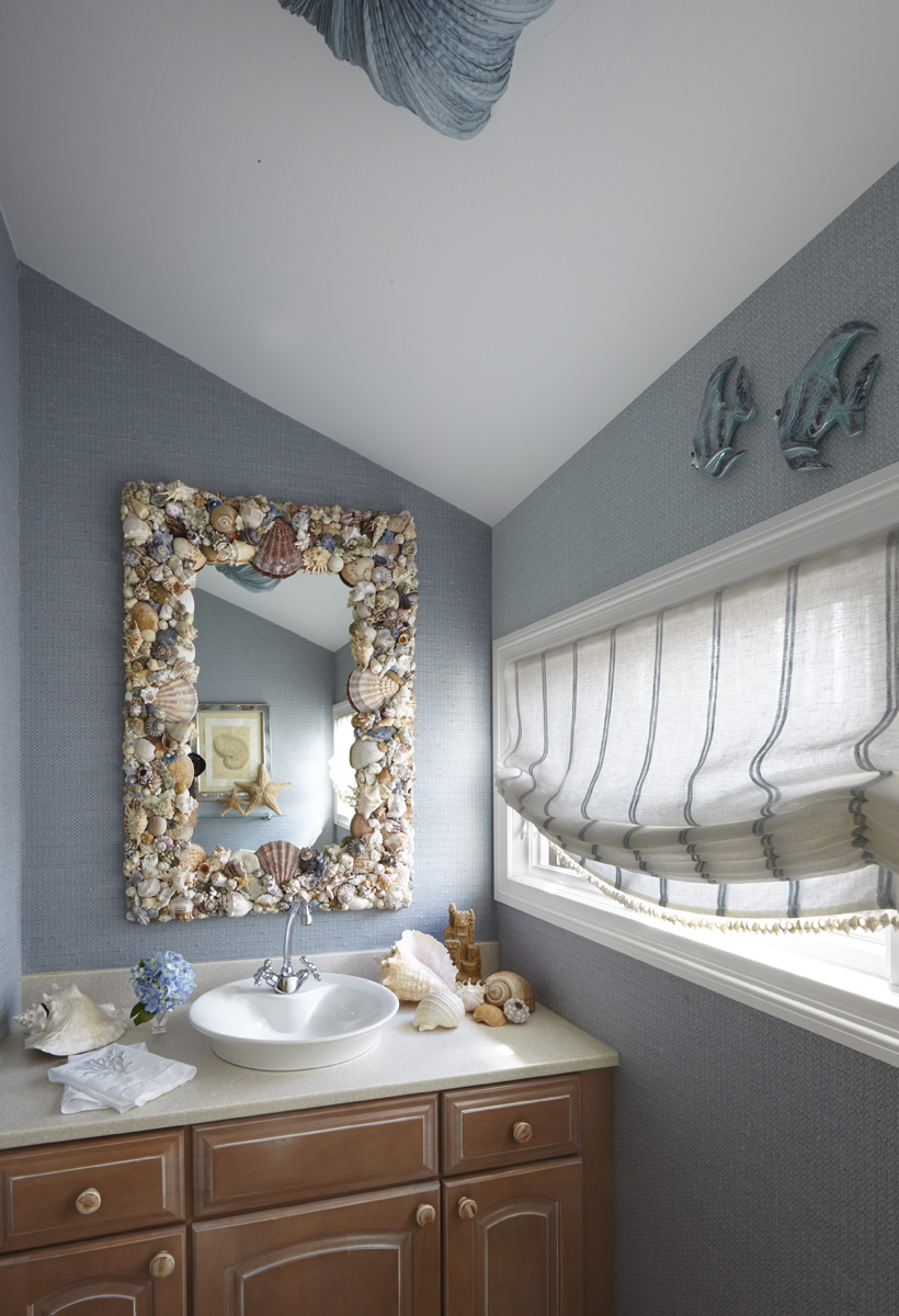 A textured phillip jefferies wallcovering in powder room. A functional striped flat roman shade. Mirror with sealife and shells.
