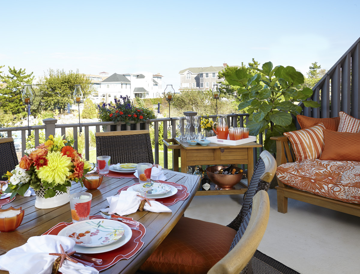 outdoor terrace with walter's wicker furniture and orange sunbrella fabrics