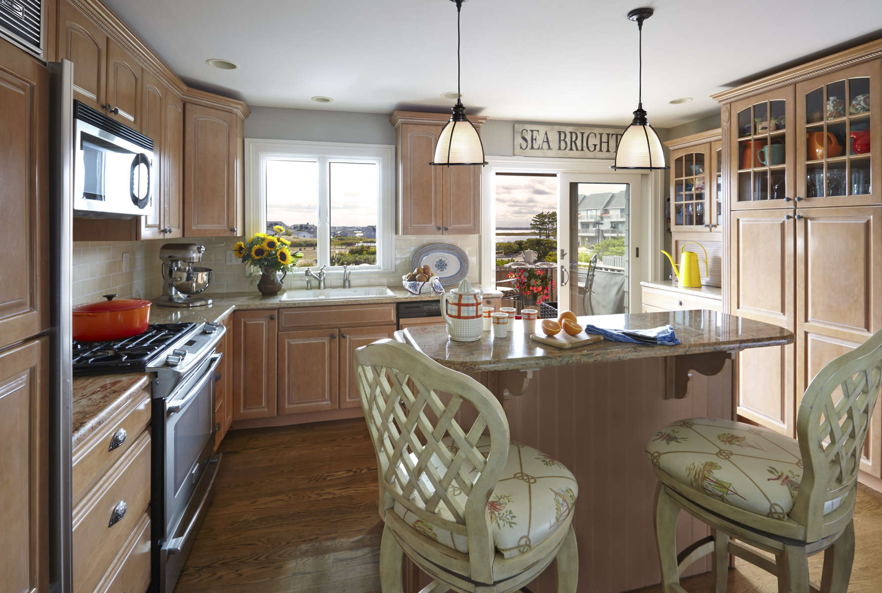 Beach house kitchen with glazed light wood cabinetry. Two height center island.