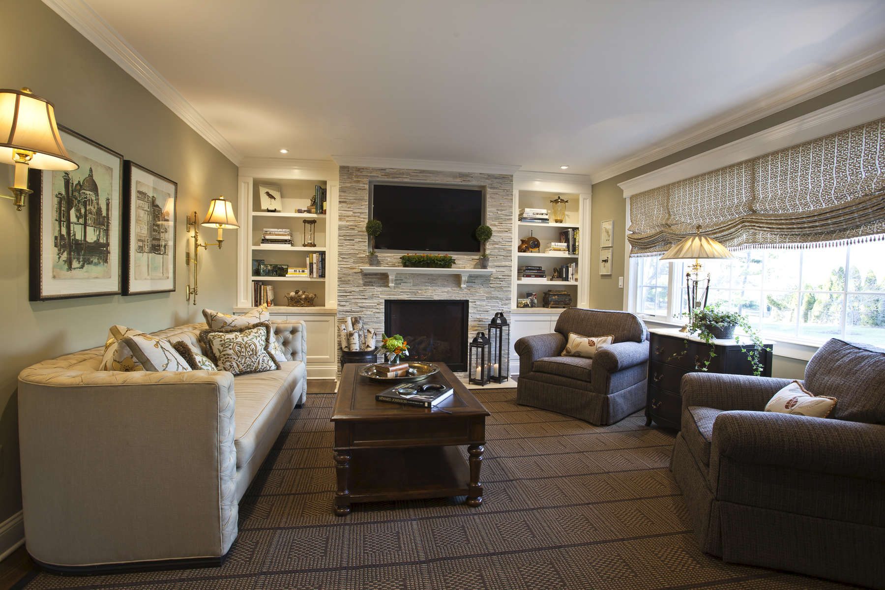 family room with white built-ins on either side of a stone fireplace