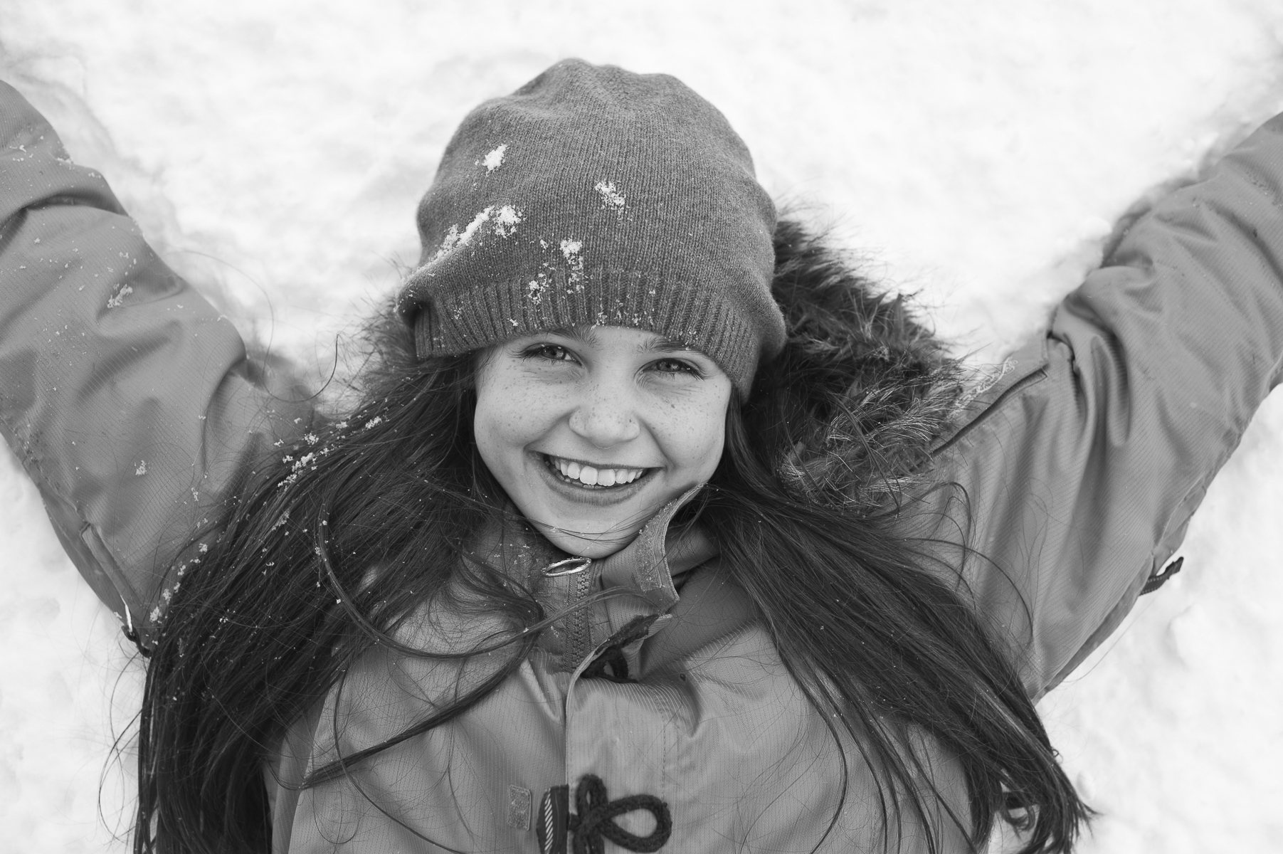 young girl making snow angel