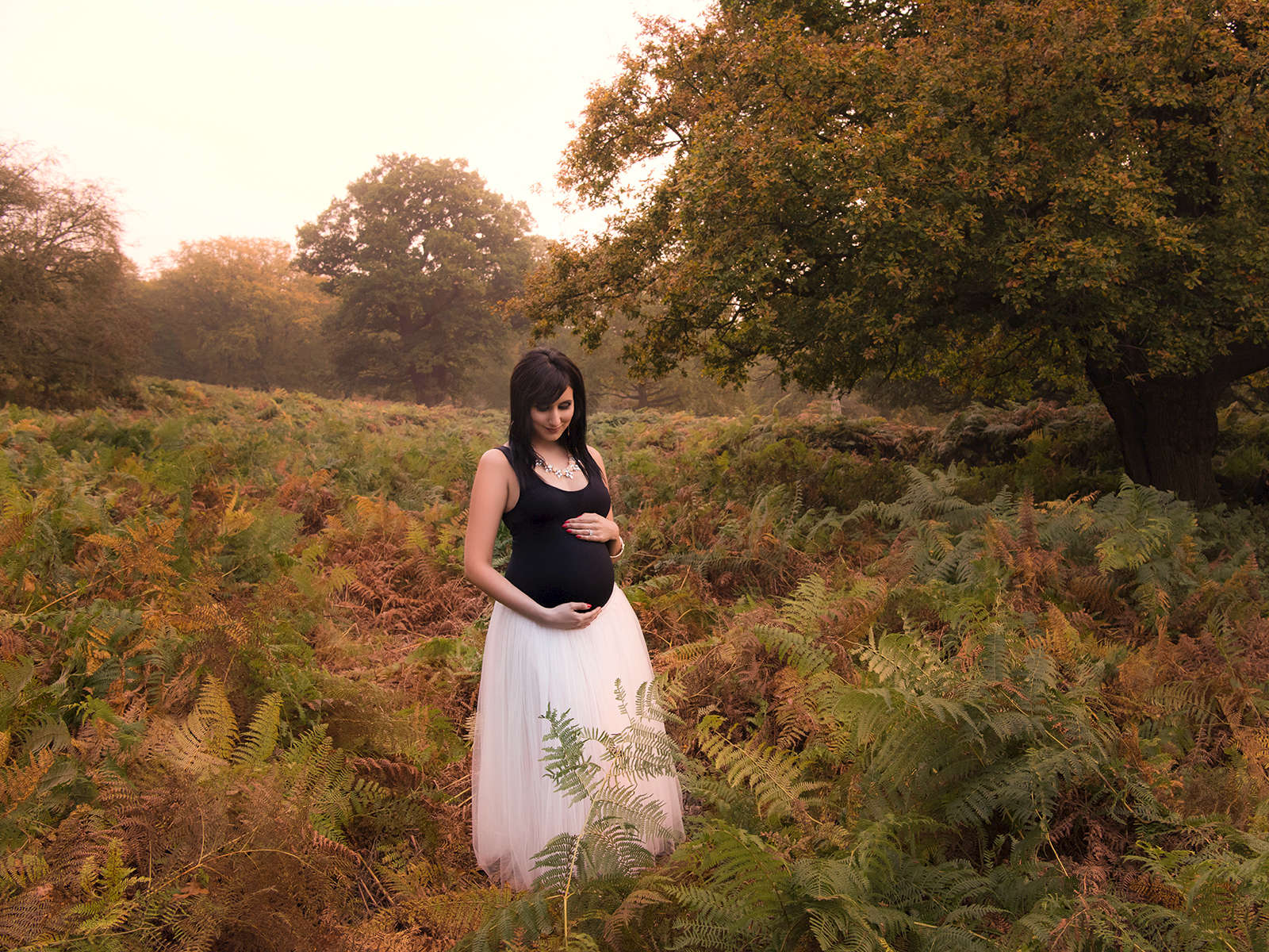 Outdoor maternity image of mum to be in long grass and woods.
