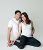Pregnancy portrait of a happy couple sitting on a floor in a studio setting.