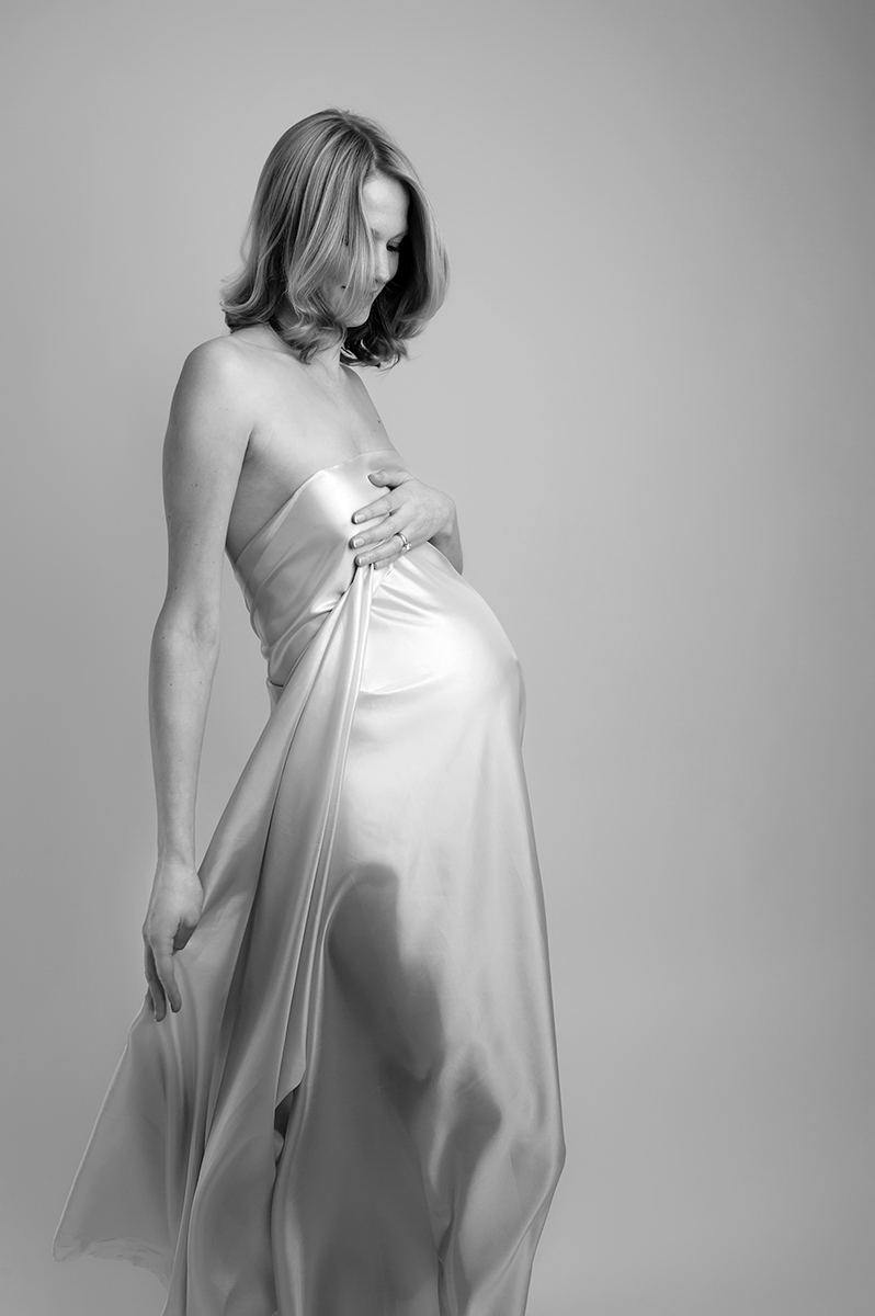 Black and white maternity photograph.  Beautiful full length artistic image of mum wrapped in flowing fabric.