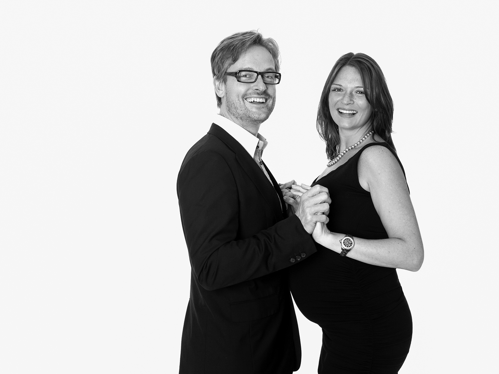 Stylish black and white photograph of an expectant couple. The image shows a couple holding each shot against  a white back drop.