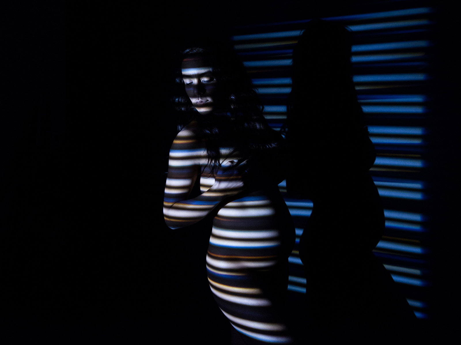 Colour maternity photograph of a nude pregnant lady standing in the shadow of a Venetian blind.