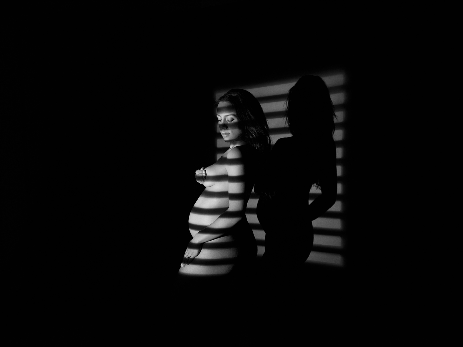 Black and white maternity photograph of a nude pregnant lady standing in the shadow of a Venetian blind. She is covering her breast with her hand.