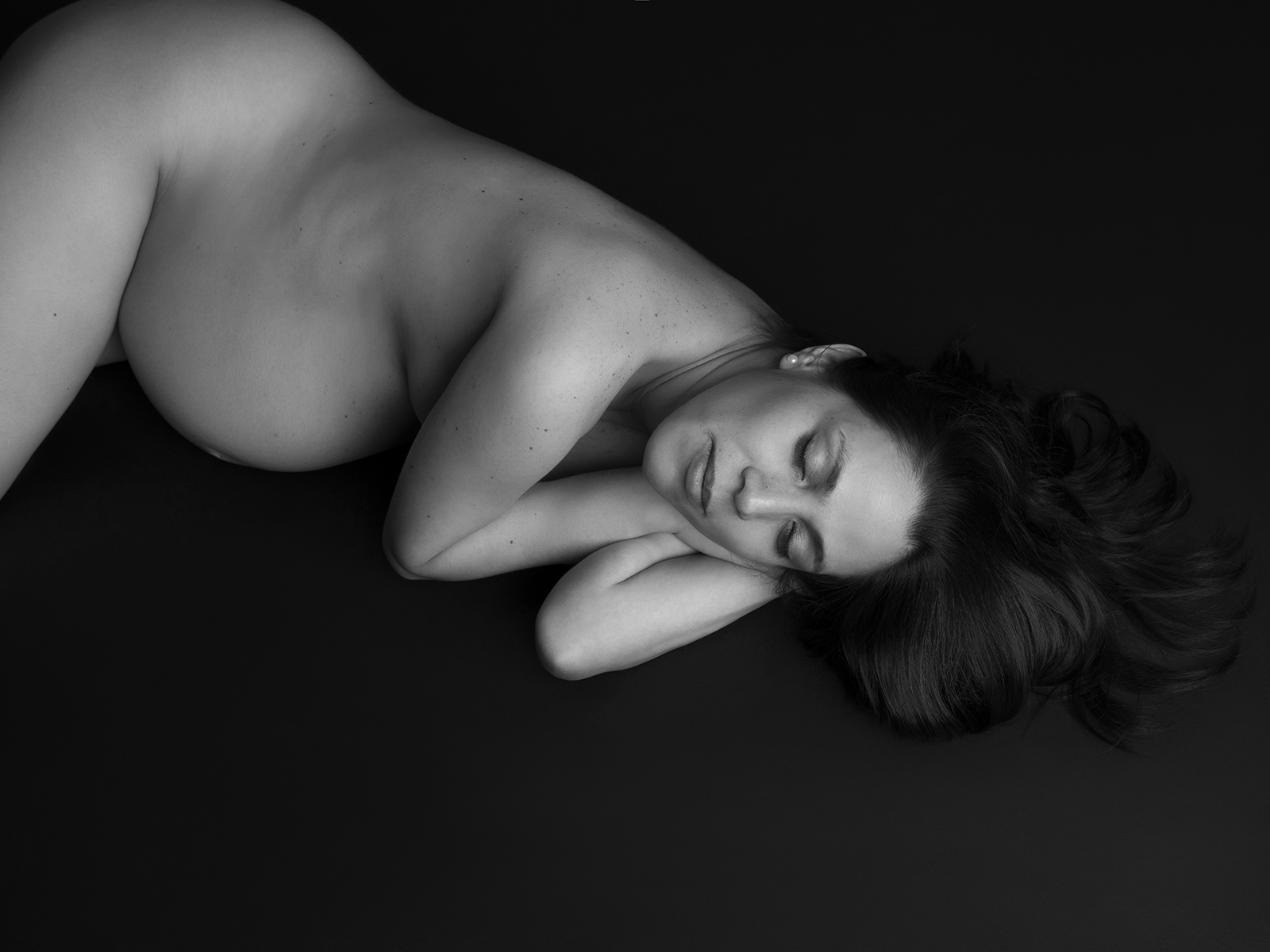 Black and white semi nude photograph of mum to be. Close up image with her laying on the floor. Black back drop used.
