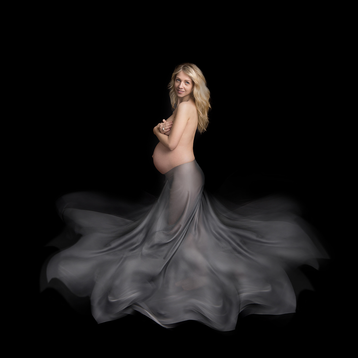 Semi nude image of a pregnant lady with long blond hair. She is wearing flowing fabric and the back ground is black.