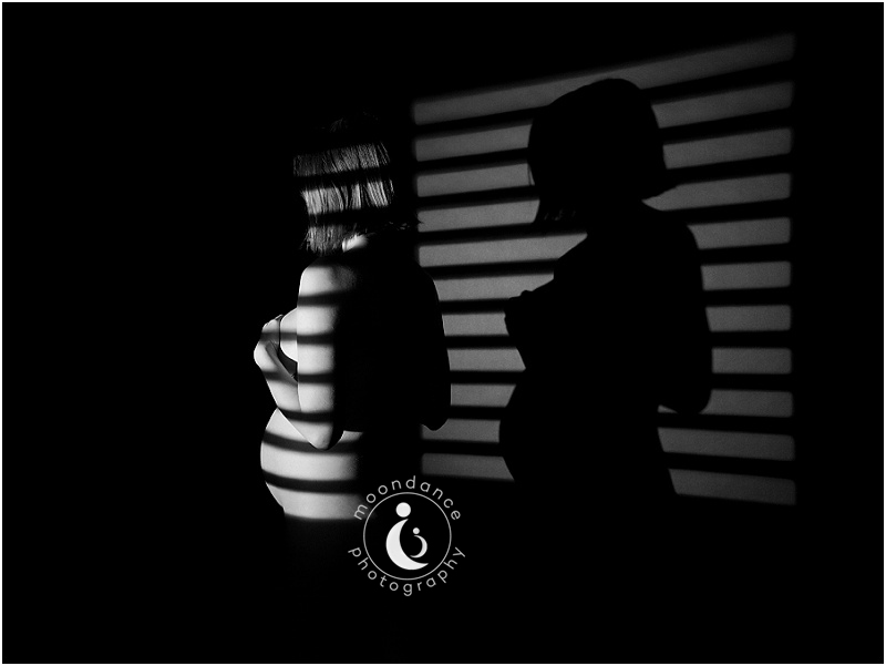 Avant-garde black and white maternity portait using chiaroscuro and zebra pattern.