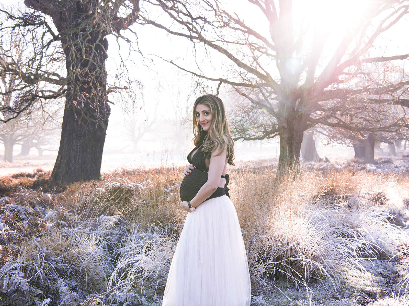 Outdoor portrait of pregnant mum to be. Mist in background.