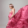 A pregnancy photography portrait with flowing drapes and a flower headdress. Photographed at Moondance Photography studio.