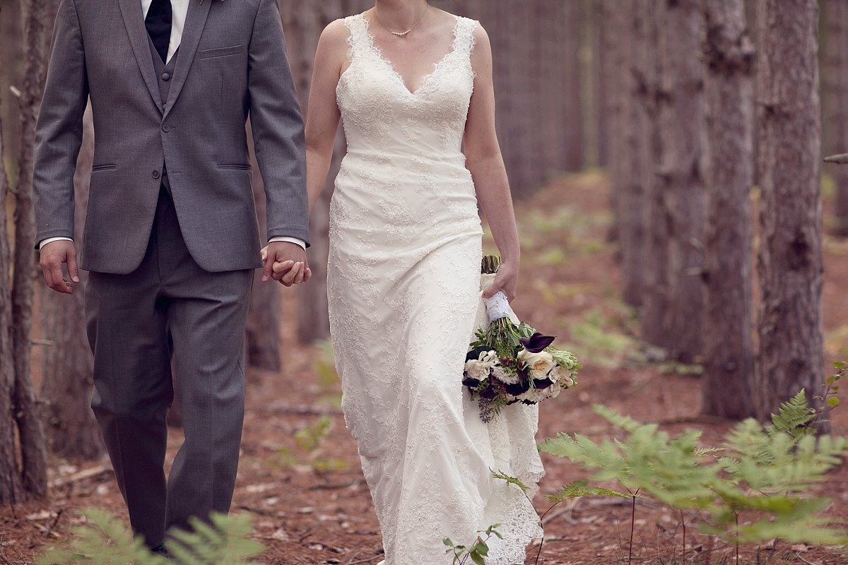 Bride and groom walking in the woods, Traverse City Michigan wedding.