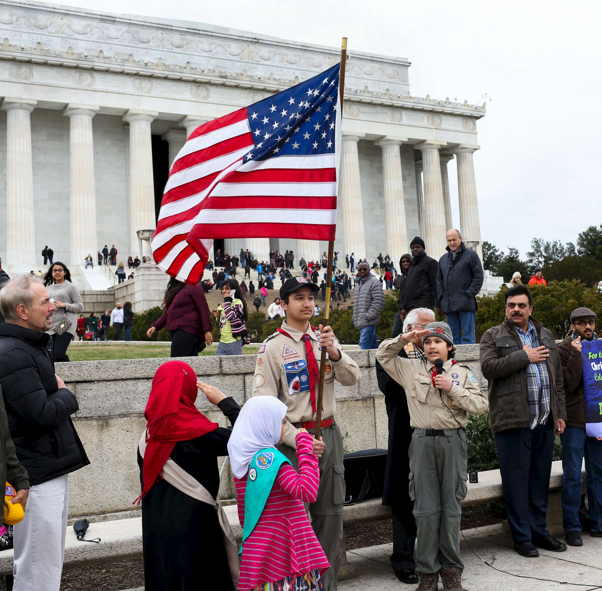 A Muslim boy scout carries the American flag as the Pledge of Allegiance is recited at an interfaith celebration of Christmas and Mawlid, an observance of the birthday of Prophet Muhammad, in front of the Lincoln Memorial in Washington, D.C., Saturday, December 26, 2015. The event, organized by the American Muslim Institution and ADAMS Center, included singing Christmas carols and songs about Prophet Muhammad.