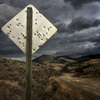 A road sign, riddled with gunshot holes, stands along a gravel road leading from Gardiner, Montana to the town of Jardine along the boundary of a Yellowstone National Park. On assignment for @natgeo in the GYE.