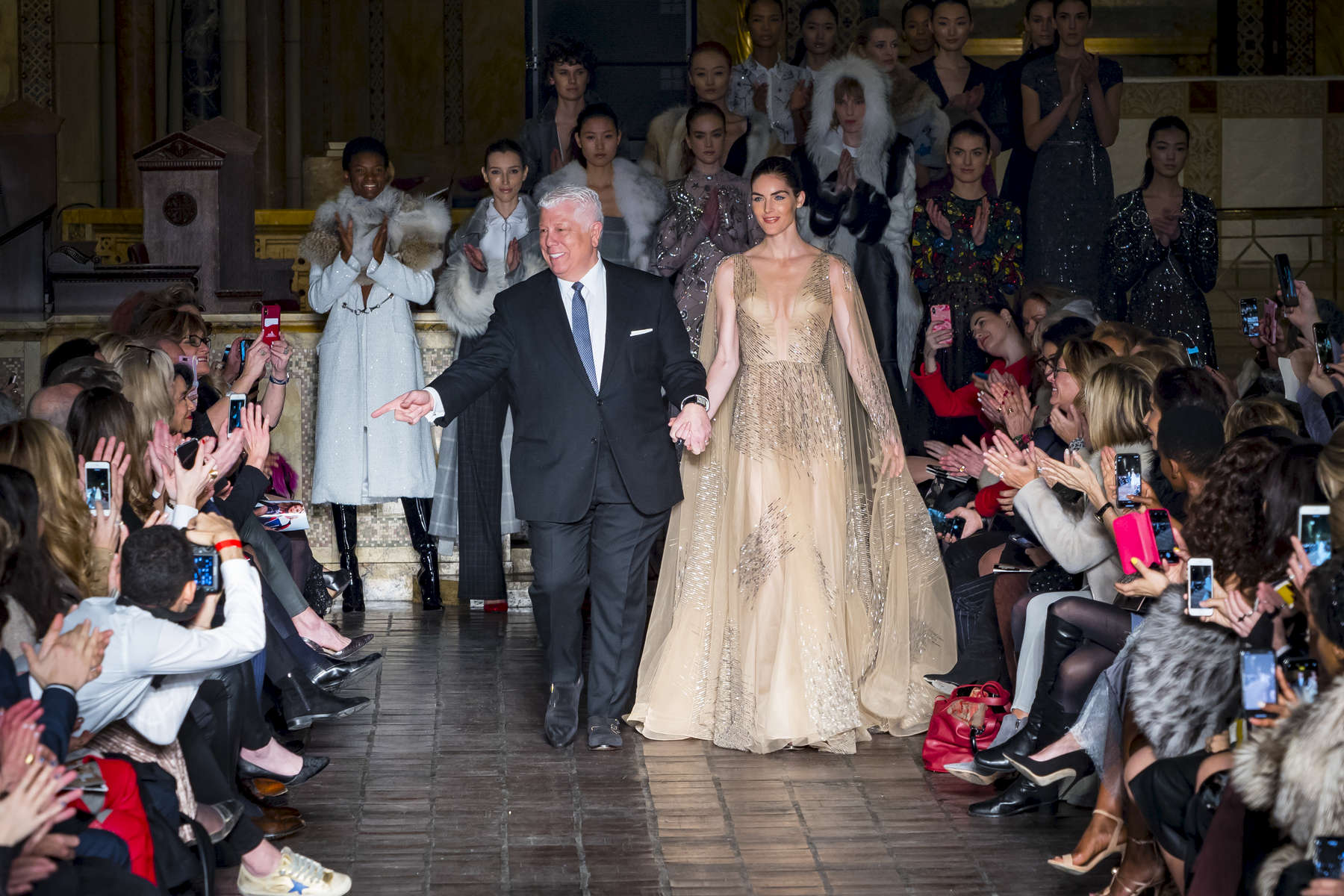 Audience applauded as designer Dennis Basso and model Hilary Rhoda walk together at the end of Dennis Basso's fashion show at the New York Fashion Week held inside Saint Bartholomew's Church located at 325 Park Avenue in Manhattan, New York on Monday, February 12, 2018.