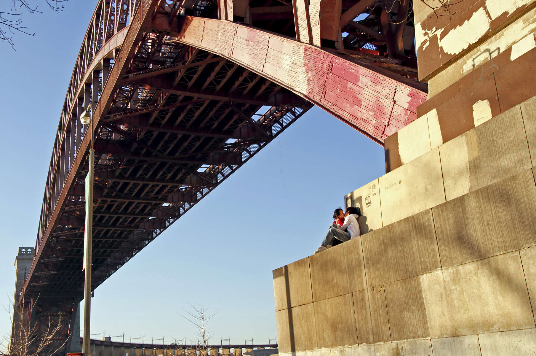 Kenneth Cuesta, 21, and Lisa Wong, 21, of Forest Hills, Queens, kiss as they watch the sunset under the Hell Gate Bridge located at Shore Boulevard in Astoria, New York on March 17, 2010.