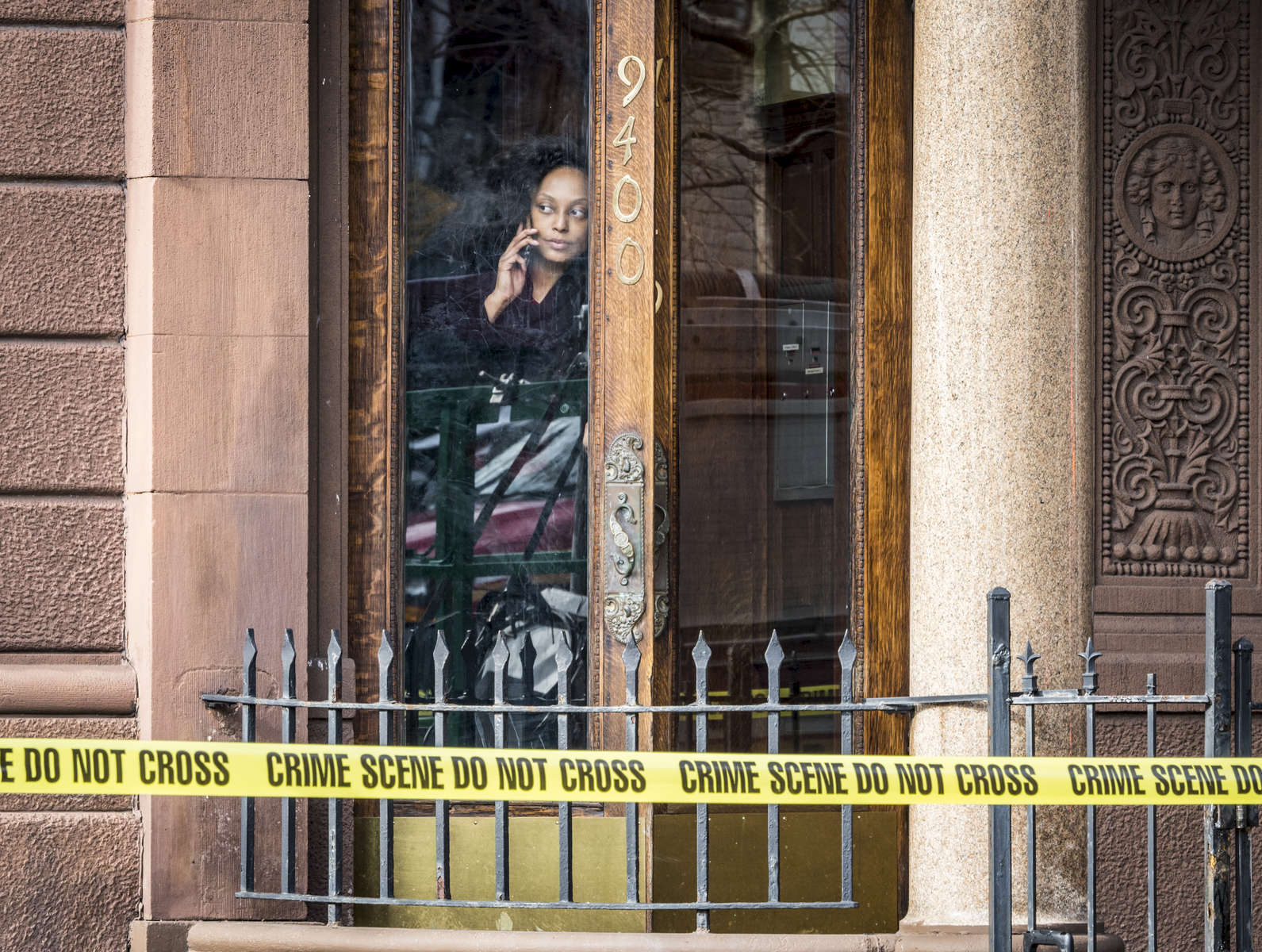 A woman looks out of her door as FDNY investigators inspect the scene where firefighter Michael Davidson, 37, was killed while battling the 5 alarm fire located at 773 St. Nicholas Avenue in Manhattan on Friday, March 23, 2018.