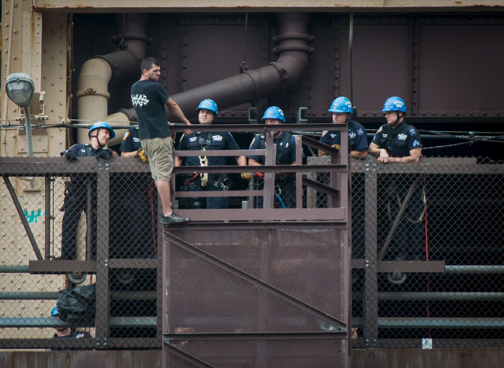 Members of the NYPD Emergency Service Unit talk down a suicidal man from the edge of Queens Borough Bridge as he threatens to jump off, down to Roosevelt Island on Tuesday, August 12, 2014.