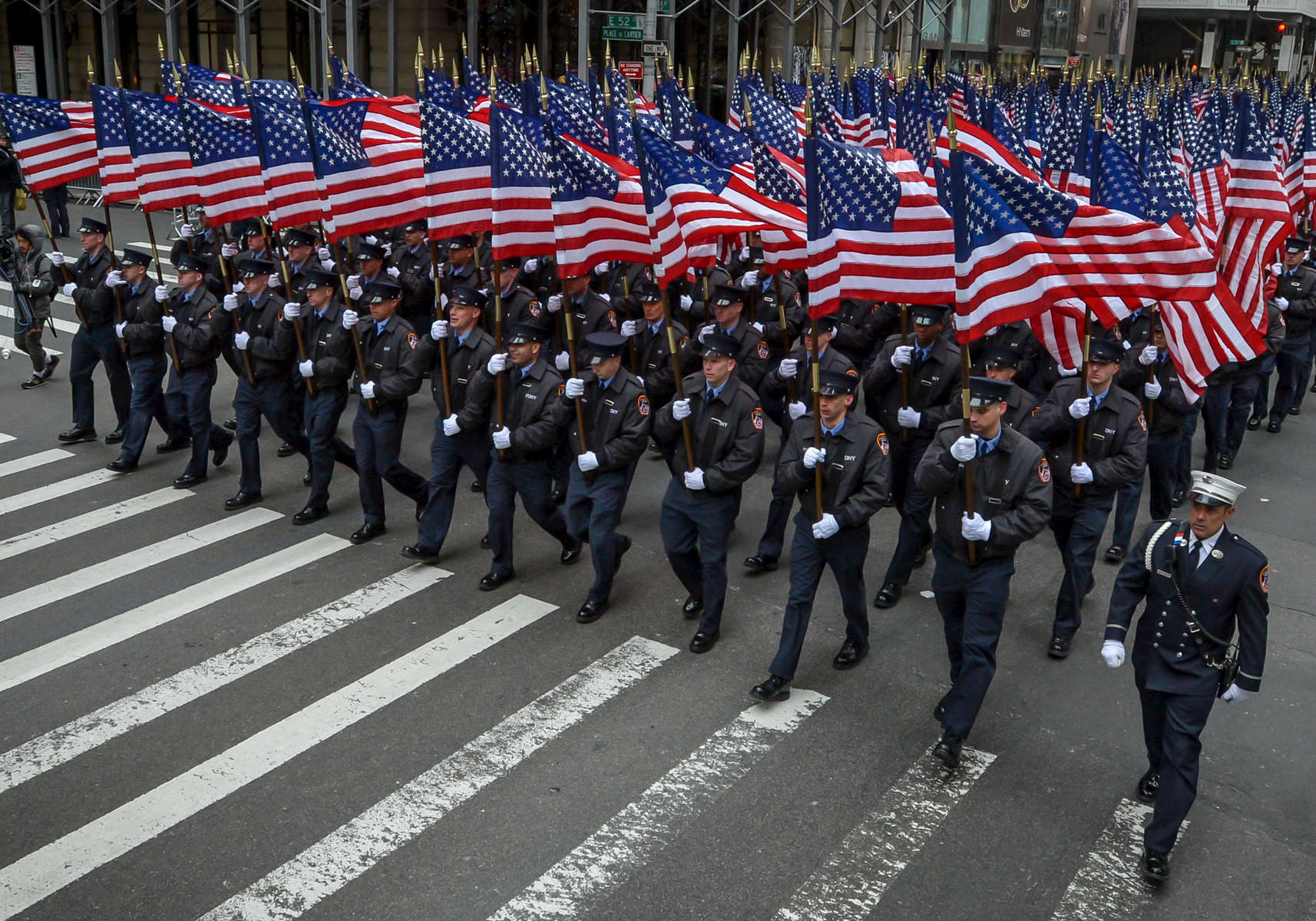 Members of the New York City Fire Department carry American flags as they march in the 253rd Annual Saint Patrick's Day Parade along 5th Avenue in Manhattan on Monday, March 17, 2014.
