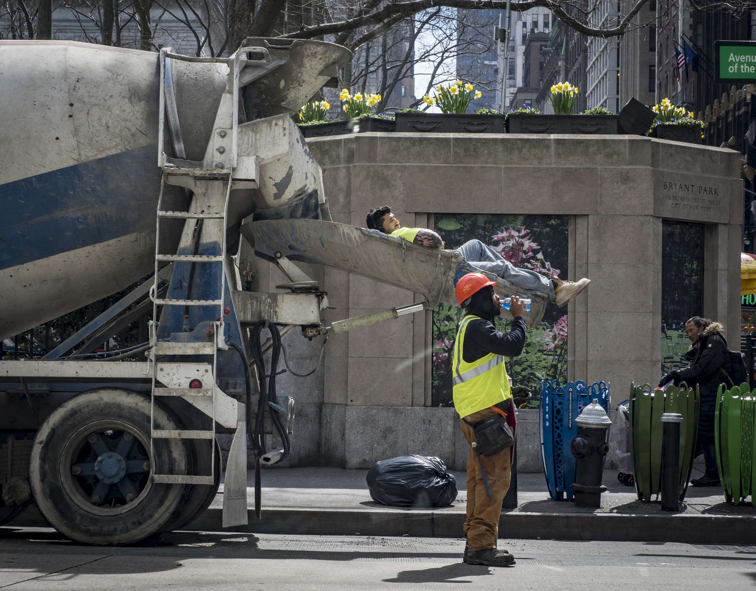 A construction worker rest on the cement truck pouring slide as he and his fellow workers take their lunch break at the corner of West 40th Street and 6th Avenue in Manhattan on Monday, April 10, 2017.