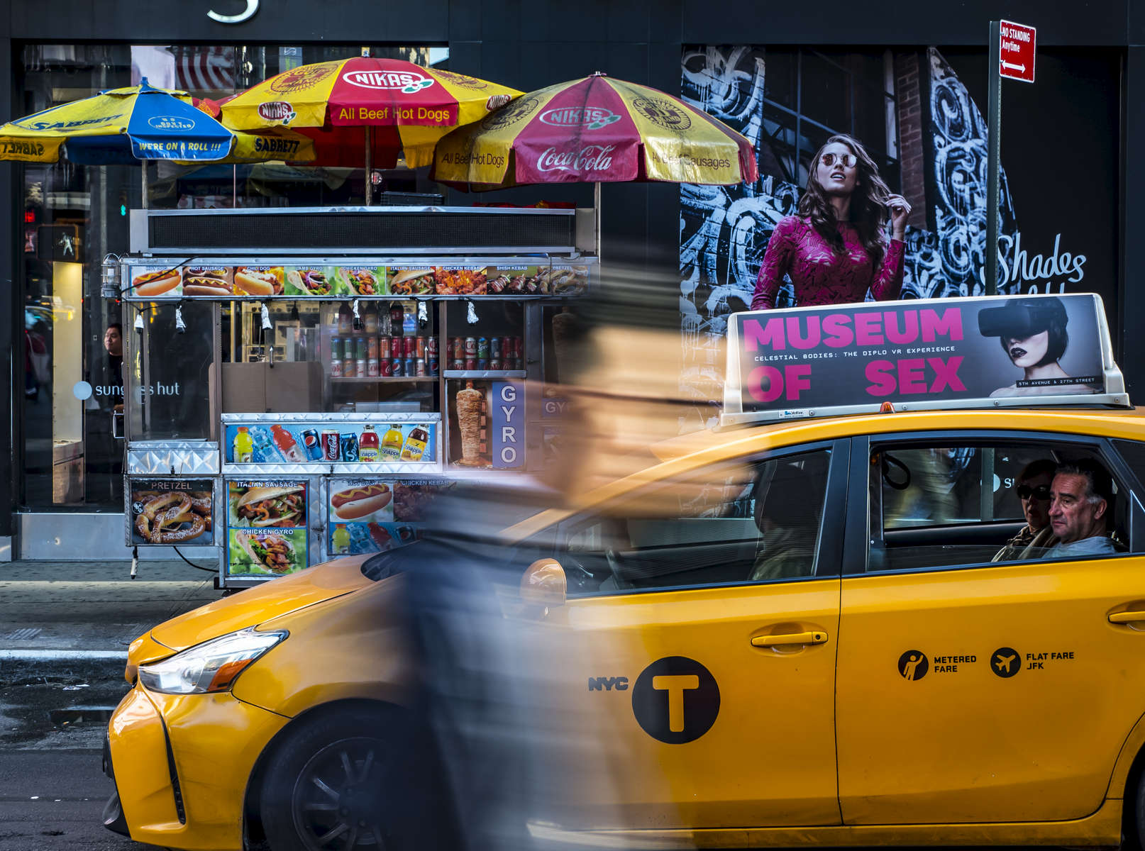A pedestrian walks by a taxi with an advertisement for the Museum of Sex on it's roof in Midtown, Manhattan on Thursday, October 19, 2017.