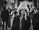 A woman in a fur hat talks on her phone and walks along 6th Avenue in Midtown, Manhattan on February 11, 2017.