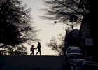 A woman and a child are both silhouetted as they cross the street early in the morning at the corner of 187th Street and Wadsworth Avenue in Washington Heights in Manhattan on Friday, December 9, 2016.