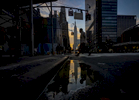The Empire State Building is reflected in a puddle while pedestrians are silhouetted against an illuminated early morning sky during sunrise at the corner of 34th Street and 8th Avenue in Manhattan on Thursday, November 3, 2016.
