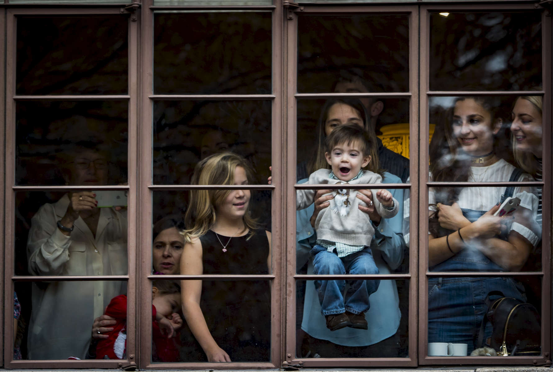 Spectators enjoy watching Macy's Thanksgiving Day Parade 2016 from their window, as participants pass along Central Park West in Manhattan on Thursday, November 24, 2016. (Anthony DelMundo/New York Daily News)