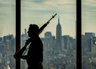 A member of the U.S. Department of Homeland Security Honor Guards is silhouetted against a backdrop of the New York City skyline as he participates on a ceremony commemorating the Federal government's return to One World Trade Center. The event was held on the 63rd floor of One World Trade Center in Manhattan on Friday, September 9, 2016.