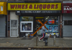 An unidentified man carries a cross as he walks past a Wines & Liquors store along Sutphin Boulevard in Jamaica, Queens on Good Friday, April 3, 2015. Good Friday is a Christian religious holiday commemorating the crucifixion of Jesus Christ and his death at Calvary.