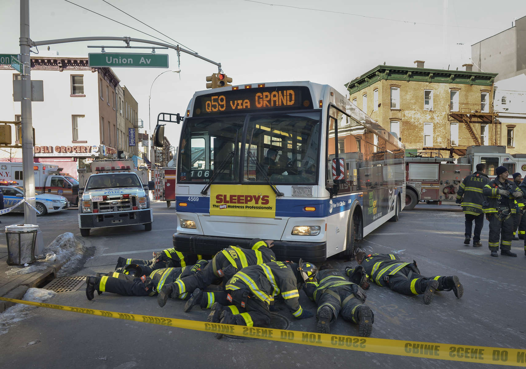 FDNY firefighters check under the MTA bus after Jiahuan Xu, 15, was struck at the corner of Grand Street and Union Street in Brooklyn on February 13, 2015. MTA bus driver Francisco de Jesus, 58, was arrested on criminal charges under Mayor Bill DeBlasio's Vision Zero plan. In a previous time he would have just received a ticket charging him with a non criminal traffic violation.