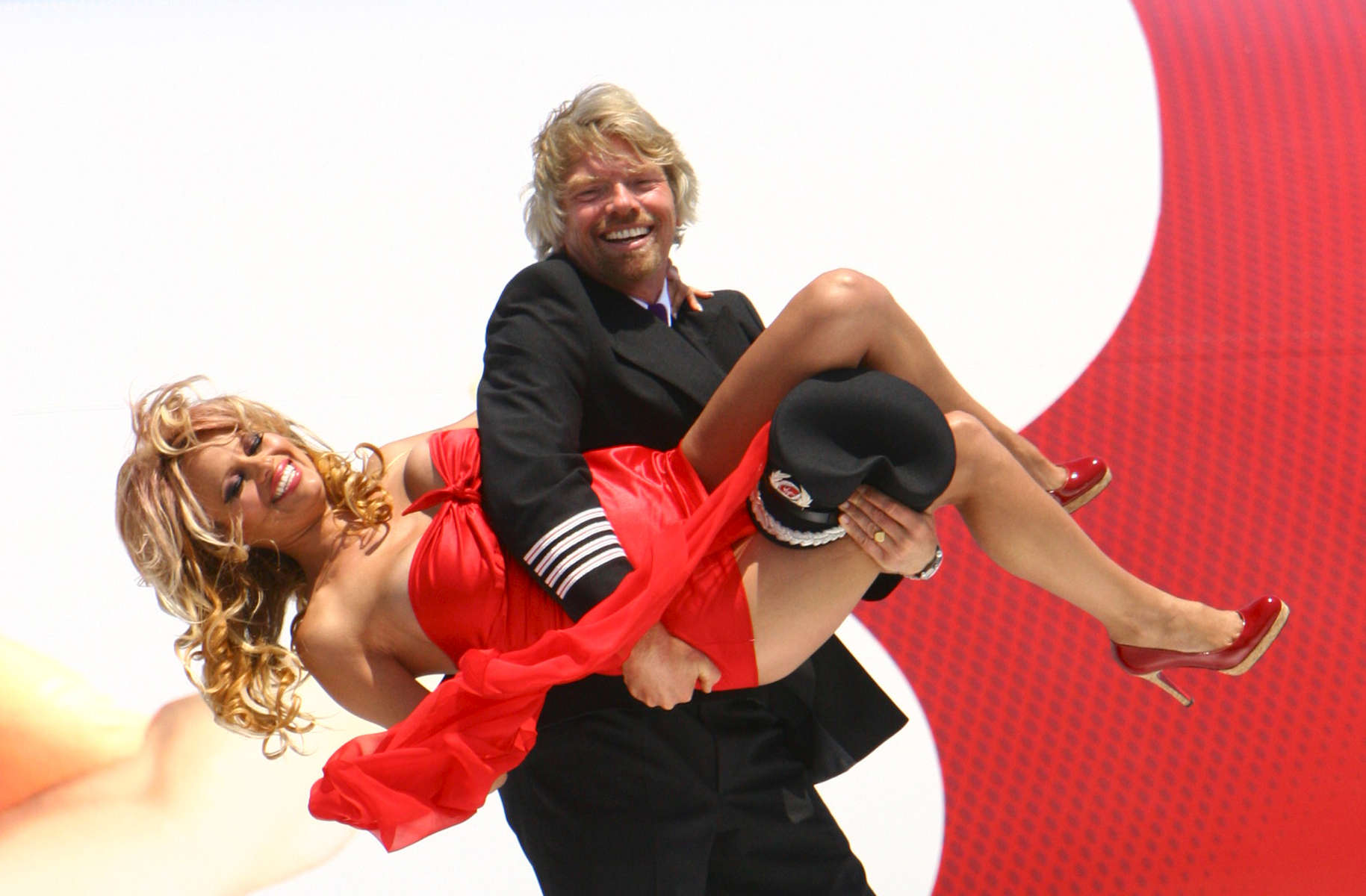 Sir Richard Branson introduces limited Edition 21st Birthday flight while he walks at the left wing of the plane with a surprise celebrity guest (Pamela Anderson) {quote}Brings to Life{quote} newly styled {quote}Flying Lady{quote} in JFK Airport terminal 4 on Wed. June 22, 2005.