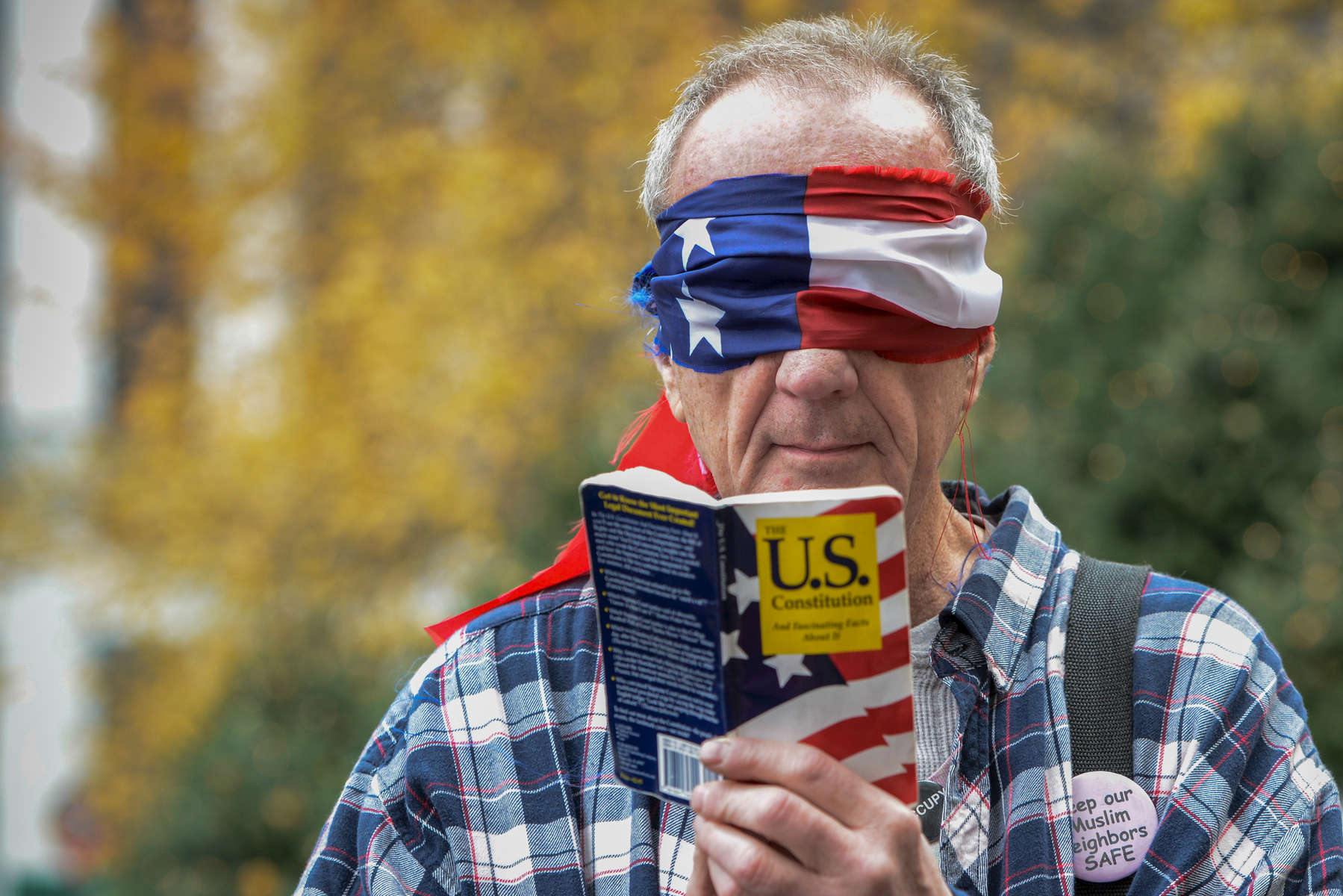 One of the protestors blindfolded himself with an American flag and and makes a gesture of reading the U.S. constitution book as he joins fellow protestors outside the Plaza Hotel as Republican presidential candidate Donald Trump speaks, located at 768 5th Avenue in midtown Manhattan on Friday, December 11, 2015.