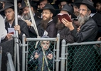 A kid looks on from behind the fence as he joins rabbis from around the world wait on line to pray at the gravesite of the Labavitcher Rebbe, Rabbi Manachem M. Schneerson at Old Montefiore Cemetery located at 226-20 Francis Lewis Boulevard in Queens on Friday, November 1, 2013. Rabbis from around the world meet in New York for the International Conference of Chabad-Lubavitch Emissaries, an annual event aimed at reviving Jewish awareness and practice around the world.