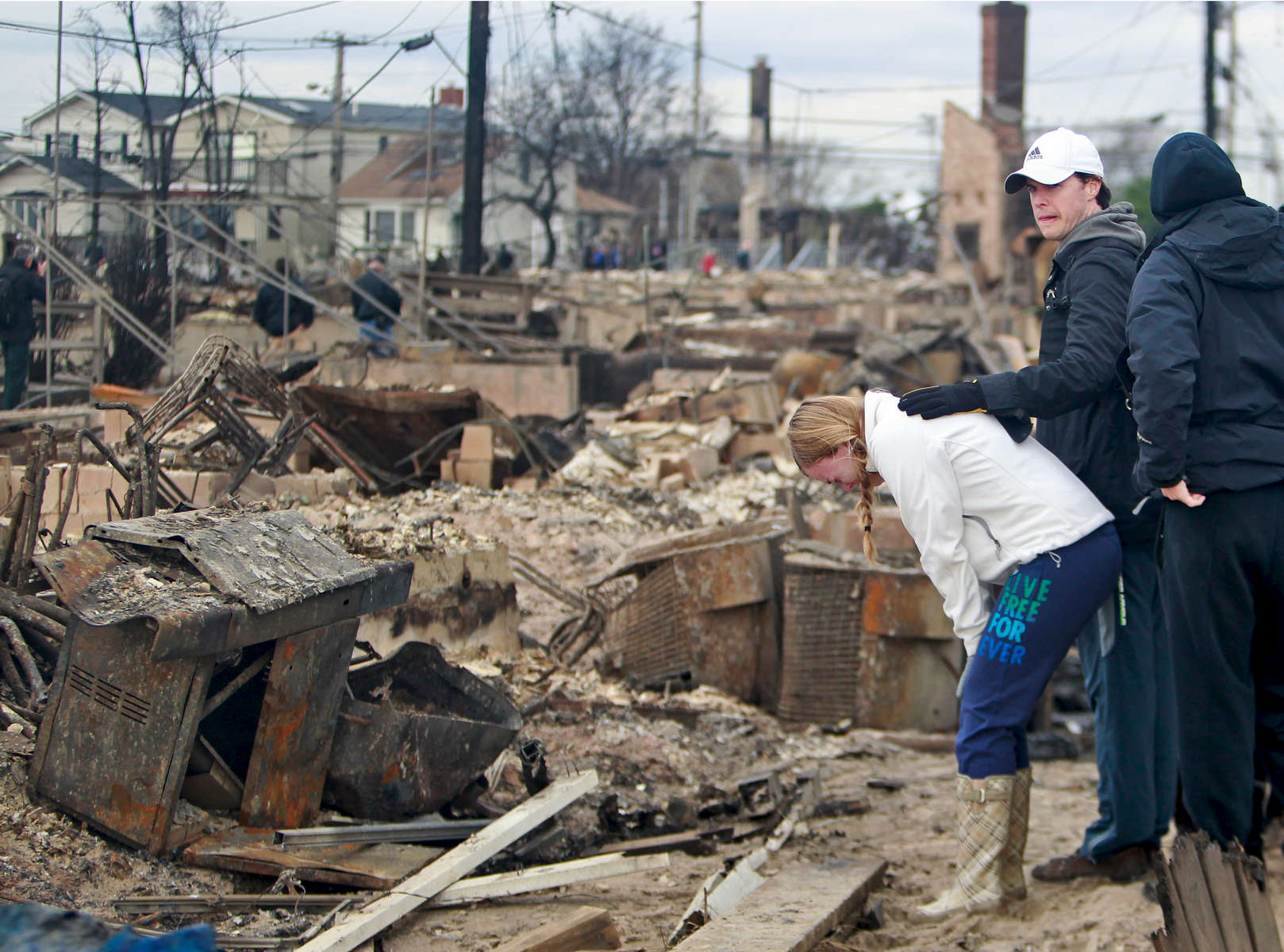 A woman weeps as she came back to see her destroyed home in Breezy Point, New York from a massive fire caused by hurricane Sandy on Wednesday, October 31, 2012.